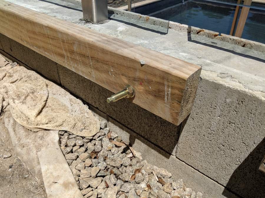 Ledger board fixed to retaining wall